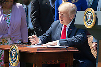 United States President Donald J. Trump signs an Executive Order to ensure that all faith-based communities have strong advocates in the White House during a National Day of Prayer event in the Rose Garden at the White House in Washington, DC on May 3, 2018. Credit: Alex Edelman / CNP /MediaPunch