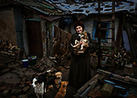 Popasna, eastern Ukraine Nov. 2017.<br /> <br /> Svetlana Nikolaevna Lebed, 62, holding her elderly dog Tuzik.<br /> <br /> Grad rockets (&lsquo;Grad' is a nickname meaning hail) hit her home 15 minutes after a ceasefire had finished on 14/2/2015, between the Ukrainian army and pro-Russian separatists&rsquo;. <br /> <br /> She was in bed when the rockets struck and is lucky to be alive, but the attack caused extensive damage to her house. With an outside temperature of -8c and no-where else to go, she was forced to stay where she was.<br /> <br /> The walls are cracked and although she has had some minor repairs done to the roof it still leaks severely. The local administration gave her two pieces of tarpaulin for the roof, but despite pleas from a neighbour on her behalf, they wouldn&rsquo;t give her enough to cover the whole roof. <br /> <br /> She bought the property eighteen years ago but doesn&rsquo;t have the official papers for its purchase and so can&rsquo;t qualify for help to rebuild it. <br /> <br /> She cannot afford the electric for heating or fuel for cooking, although sometimes a neighbour from the next village will bring her some hot food. She doesn't receive any support from anyone else.<br /> <br /> Without the necessary repairs to the building, she fears it will fall down and she will be forced to go into an old people&lsquo;s home. &lsquo;I ask God to let me live longer for the sake of my dogs'.