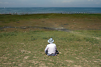 A tourist looks out onto the shores of Qinghai Lake. Qinghai Lake, China's largest inland body of water lies at over 3000m on the Qinghai-Tibetan Plateau. The lake has been shrinking in recent decades, as a result of increased water-usage for local agriculture. Qinghai Province. China. 2010