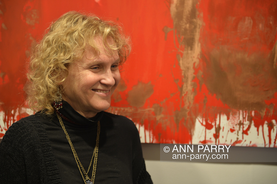 Huntington, New York, U.S. - March 1, 2014 - At the Opening Reception '3 Wild and Crazy Artists' at FotoFoto Gallery, a woman visitor smiles at the exhibit 'Red & White Paintings & Photographs – El Vocio Existential' by artist Barry Feuerstein.