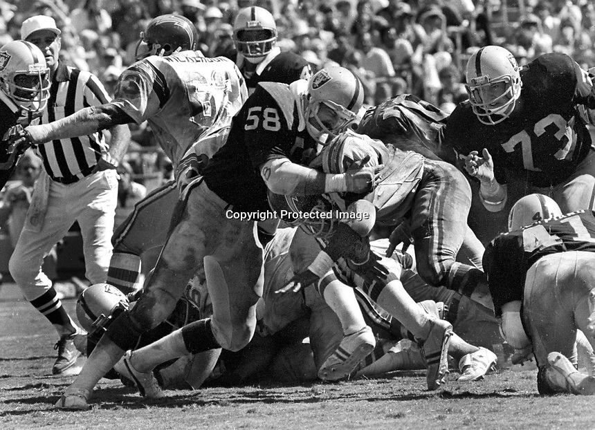 San Diego Charger       is stopped by Raider linebacker Monte Johnson, and #73 Dave Browning. (1978 photo/Ron Riesterer)