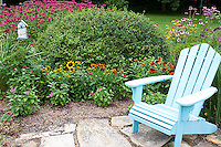 63821-206.15  Blue chair and birdhouse in garden with  Autumn Colors Black-eyed Susans (Rudbeckia hirta 'Autumn colors'), Red and Pink Pentas (Pentas lanceolata), Butterfly Bush (Buddleia davidii), Raspberry Wine Bee Balm (Monarda didyma) Marion Co. IL
