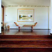 An antique carved cane bench stands beneath a framed landscape on this raised landing