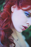Close up of pretty young woman's face staring at camera with bright blue eyes and red hair