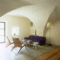 An informal sitting room with a low vaulted ceiling and stone tiled floor. The room is furnished with a purple sofa and wood armchairs. A low coffee table stands between them.