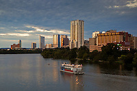 Skyline of Austin, Texas with Lake Austin, Colorado River and riverboat in foreground amid soft pillow clouds among the heavens.