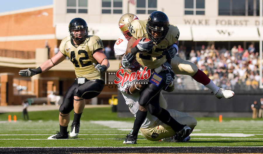 WINSTON SALEM, NC - NOVEMBER 14:  Josh Adams #27 of the Wake Forest Demon Deacons drags two Florida State Seminole defenders into the end zone as he scores on a 3 yard run at BB&T Field on November 14, 2009 in Winston Salem, North Carolina.  The Seminoles defeated the Demon Deacons 41-28.  Photo by Brian Westerholt / Sports On Film