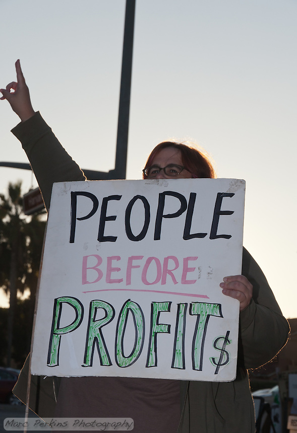 """A woman flashes the peace sign whiel holding a """"People Before Profit$"""" sign at the Occupy Orange County - Irvine camp."""