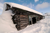 An abandoned cabin rests coldly in the snow on Diamond Ridge overlooking Homer, Alaska.