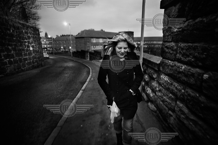 Rona walks down a street. Rona from Gourock is a heroin addict and one of six women accepted on a pioneering trial in Glasgow of NET (NeuroElectric Therapy) a drug free detox device that reduces cravings and withdrawal symptoms using a small electric current.
