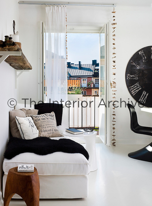 Rustic, handmade furnishings, such as the rough wooden shelf and curtain decorations, contrast with the contemporary style of this black and white apartment