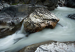 The greyish-white colored Nigel creek flowing around the river rocks in Banff National Park