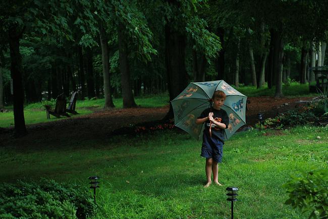 Young Boy Standing under an Umbrella in a Summer Rain Shower