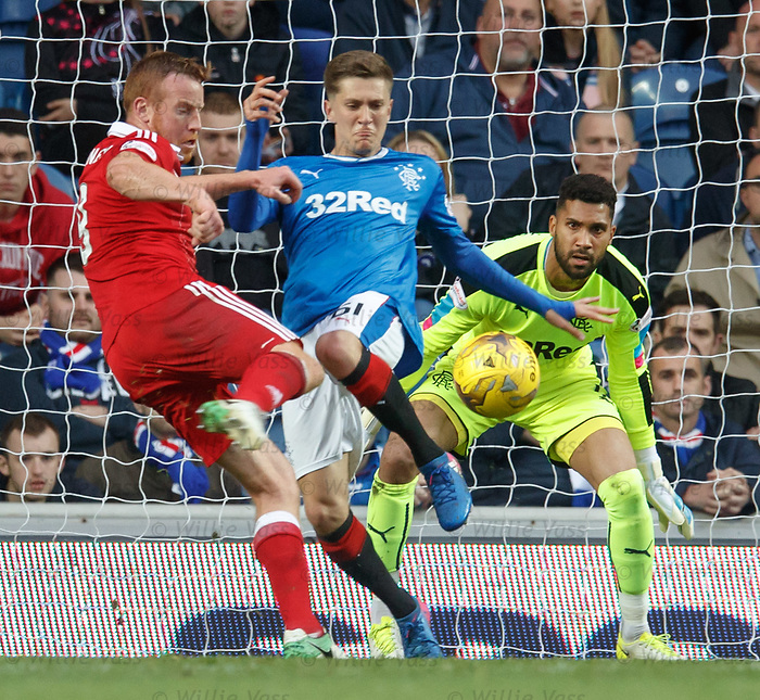 Wes Foderingham watches as Myles Beerman puts off Adam Rooney in front of goal