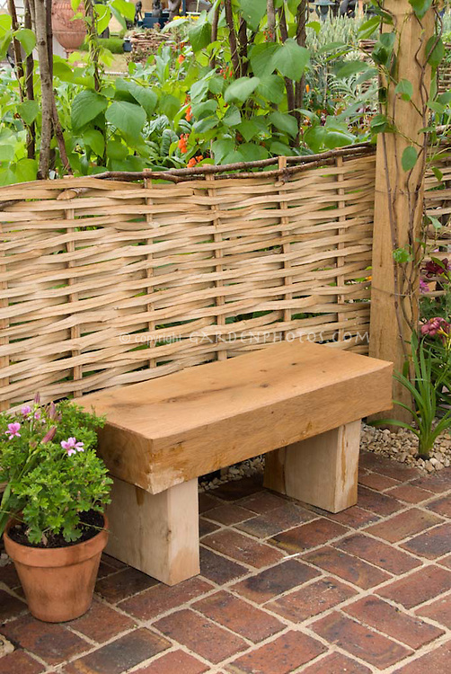 Wooden Garden Bench Against Willow Woven Fence In