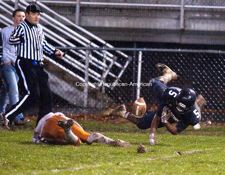 ANSONIA, CT--- -120115JS12--After getting tripped up by Capital Prep's Jahkai Gill (23), Ansonia's Tyler Bailey (5) fumbles the ball during their Class S Quarterfinal game Tuesday at Jarvis Stadium in Ansonia. <br /> Jim Shannon Republican-American
