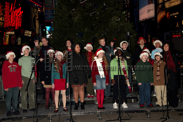 Avenue Q Cast Members, Foa Barratt, Carmen Ruby Floyd & Jennifer Barnhart with students from the Professional Performing Arts School help light the 2004 Broadway Holiday Tree at Duffy Square in Times Square, New York City..December 8, 2004.© Walter McBride /