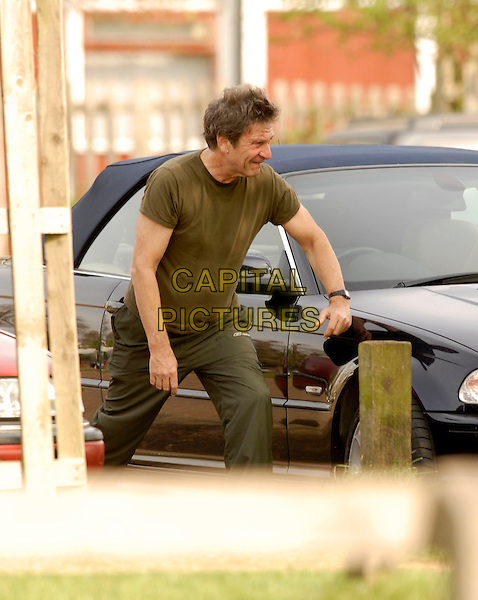 MICHAEL BRANDON.Limbering up in Richmond Park, London, .17th April 2007..half length 3/4  green khaki t-shirt t shirt stretching exercising working out tracksuit bottoms leaning on car.CAP/P8.©Capital Pictures.