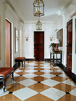 The apartment opens with a burst of colour, a wide awake shade of orange fabric by Schumacher on the cushions of a pair of custom made black lacquer benches. The orange theme continues with the lamps atop a Napoleon II console and the diamond pattern marble floor.