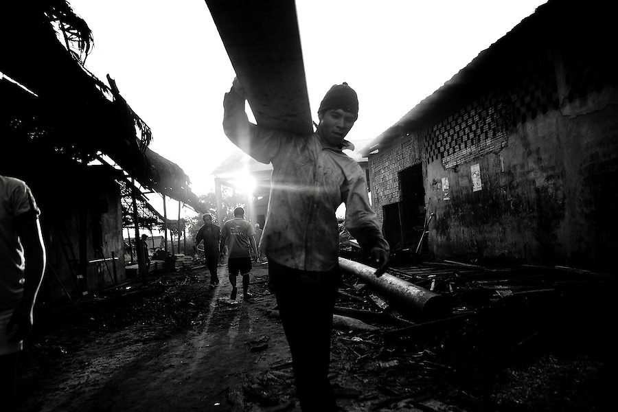 """Iquitos, Peru, Jan. 13, 2007 - Carrying scrap lumber from a mill, Hector Pas Solano hopes to use the 'unusable' material to finish the floor in his home in Belen, a small poverty-stricken area built along the flats of the Amazon River. It is comprised of homes built on stilts or of floating balsa wood. During the wet months between November and June, the Amazon can rise as much as a meter per month. He says the wood is very expensive to him, but that now that he has work as a part time jungle guide, he can afford it. """"It is for my family,"""" he adds. The processed lumber from the jungle is shipped all over the world, and is the largest export for the region. Scrap that is deemed' unusable is sold to locals for building or for fire wood. .."""