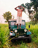 SRI LANKA, Asia, guide with shielding eyes standing on a jeep at Udawalawe National Park