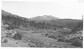 Looking NE toward Parrott Peak.  RGS grade near MP 140 on hillside above power line and old highway in foreground.<br /> RGS  Cima, CO  Taken by Maxwell, John W. - 8/16/1962