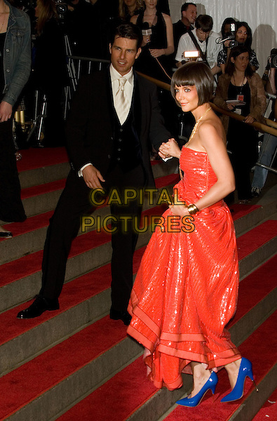 "TOM CRUISE & KATIE HOLMES.Costume Institute Gala - ""Superheroes: Fashion and Fantasy"" at The Metropolitan Museum of Art, New York, NY, USA..May 5th, 2008 .full length black suit red strapless dress gold necklace married husband wife blue shoes white clutch bag purse holding hands .CAP/LNC.©TOM/LNC/Capital Pictures."