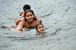 THOMASTON, CT-4 July 2014-070414EC03--   Marielyz Lopez and, behind her, Neysha Herrera, swim in the rain Friday afternoon at Black Rock Park in Thomaston. The showers didn't stop many families from enjoying their traditional Fourth of July activities. Erin Covey Republican-American