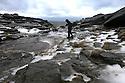 01/02/14<br /> <br /> A walker crosses the frozen Kinder river high up in the Derbyshire Peak District.  <br /> <br /> F Stop Press.  www.fstoppress.com. Tel: +44 (0)1335 300098