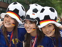 Germany, DEU, Dortmund, 2006-Jun-22: FIFA football world cup (USA: soccer world cup) 2006 in Germany; three female Japanese football fans in good mood posing with hats and stickers in German national colours before the world cup match Japan vs. Brazil (1:4).