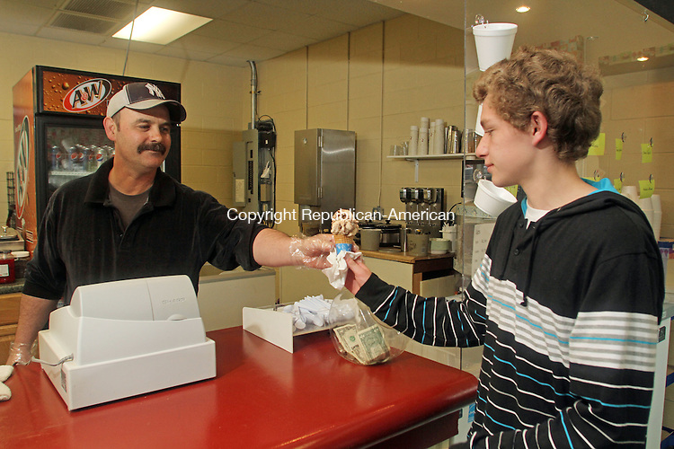 Winsted, CT-052513MK02 Terry Winn hands a peanut butter ice cream cone to customer Nate Godden, from Torrington, in Winn's new ice cream shop at the former Hogie's Sweet Shoppe at 6 Willow St. Winsted on Saturday afternoon. Winn, with the much appreciated help from family and friends, opened the ice cream shop on Friday and has changed the name to The Ice Cream Man. The shop sells Milford-based Buck's Ice Cream and sundaes come with fresh fruit. Hours are 2 to 9 p.m., Monday through Thursday, 2 to 10 p.m. on Fridays, and noon to 10 p.m. on Saturdays and Sundays. Michael Kabelka Republican American