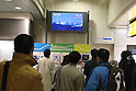 March 17, 2011, Tokyo, Japan - Commuters at Shinbashi Station in Tokyo pause to watch the TV news as they brace for a possible power outage planned in an attempt to conserve electricity. The power grid has been impacted heavily by the recent earthquake and its aftermath. (Photo by YUTAKA/AFLO) [1040].