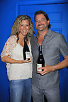 "General Hospital Laura Wright ""Carly"" poses with her husband John Wright and hold Standing Sun Wines at a Wine Tasting for Standing Sun Wines on August 11, 2012 at MaGooby's Joke House in Timonium, Maryland. The fans got a chance to takes all the various wines, a Q&A, photos, autographs. (Photo by Sue Coflin/Max Photos)"