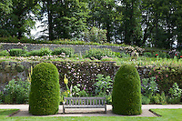 Two topiary yew bushes flank a wooden bench in the Upper Garden at Haddon Hall