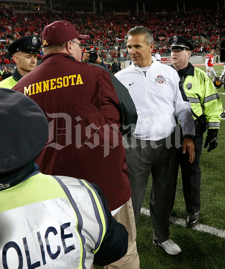 Minnesota Golden Gophers head coach Tracy Claeys and Ohio State Buckeyes head coach Urban Meyer shakes hands at midfield following Saturday's NCAA Division I football game at Ohio Stadium in Columbus on November 7, 2015. Ohio State won the game 28-14. (Dispatch Photo by Barbara J. Perenic)