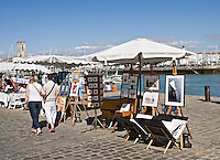 Artists selling paintings in the old part of the city of La Rochelle Charente-Maritime France  .