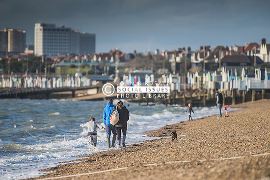 A family walk along the shoreline of Thorpe Bay beach in Southend on Sea, Essex, UK.