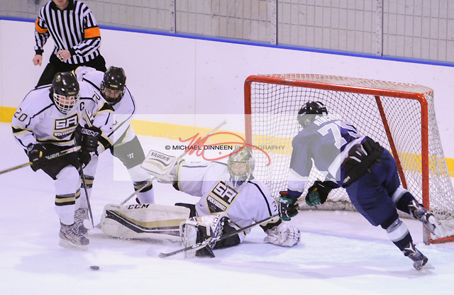 Eagle River's Ben Rinckey reaches for a rebound from Service goalie Hannah Hogenson as a pair of Cougar defenders close in on the puck during the Wolves' 2-2 tie with Service at Ben Boeke Arena Thursday, November 17, 2016.  Photo for the Star by Michael Dinneen