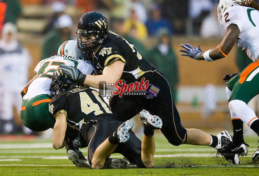 WINSTON-SALEM, NC - OCTOBER 31:  Miami Hurricanes quarterback Jacory Harris #12 is sacked by Joey Ehrmann #40 and John Russell #51 of the Wake Forest Demon Deacons at BB&T Field on October 31, 2009 in Winston-Salem, North Carolina.  The Hurricanes defeated the Demon Deacons 28-27.  Photo by Brian Westerholt / Sports On Film