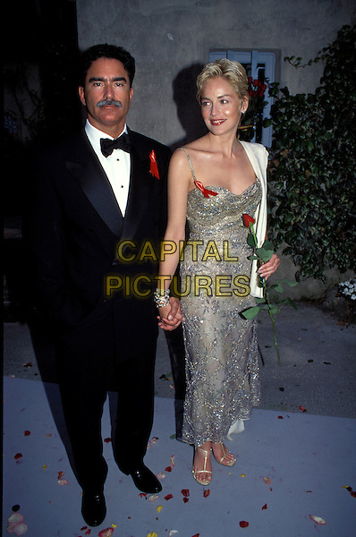 SHARON STONE  & PHIL BRONSTEIN.Ref:7424PL.black tuxedo, red ribbons, silver dress, spaghetti strap, rose, flower full length holding hands husband wife.sales@capitalpictures.com.www.capitalpictures.com.©Capital Pictures.