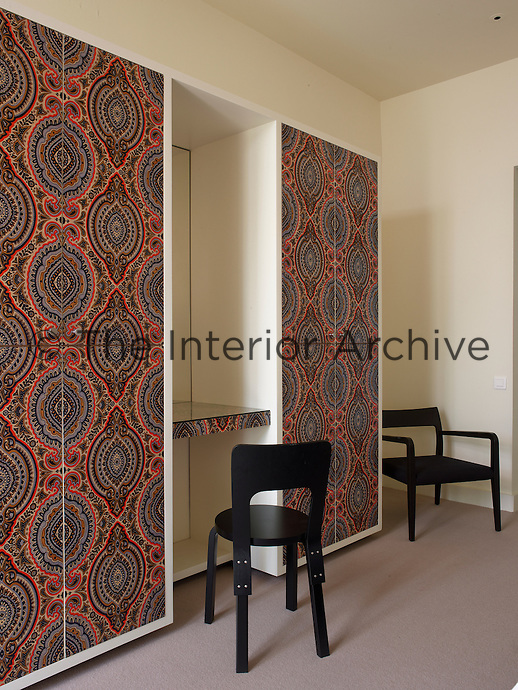 Patterned wallpaper designed by Eley Kishimoto covers the doors of the free-standing wardrobe in a guest bedroom