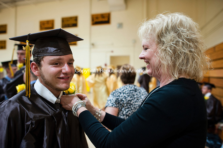 THOMASTON, CT-18 June 2014-061814EC01-  Walter LaGrave gets help from teacher Michelle Dayton before Thomaston high school's graduation Wednesday night. Erin Covey Republican-American