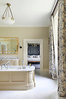 A cream ensuite bathroom with a panelled bath placed in the centre to make the most of views from the window
