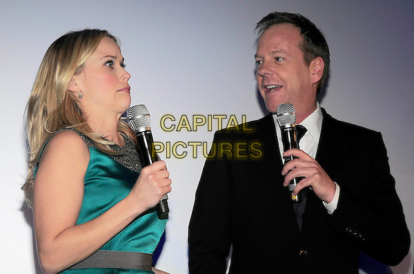"REESE WITHERSPOON & KIEFER SUTHERLAND.Premiere of ""Monsters vs. Aliens"", UCI Colosseum Kino, Berlin, Germany..March 9th, 2009.half length blue green turquoise silk satin sleeveless dress grey gray microphone black suit jacket funny face profile .CAP/PPG/NK.©Norbert Kesten/People Picture/Capital Pictures"