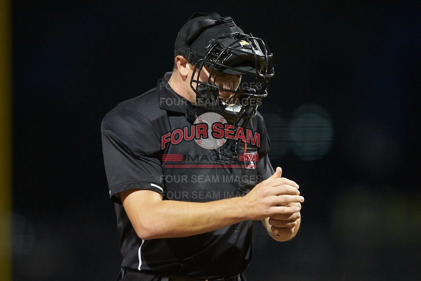 Home plate umpire Nolan Early checks a baseball during the South Atlantic League game between the Rome Braves and the Columbia Fireflies at Segra Park on May 13, 2019 in Columbia, South Carolina. The Fireflies defeated the Braves 6-1 in game two of a doubleheader. (Brian Westerholt/Four Seam Images)