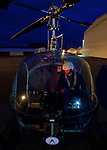 A male pilot is lit by instrument lighting in the cockpit of a Hiller helicopter at night.