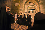 A Muslim man walks through as Greek-Orthodox Christian nuns walk along Via Dolorosa in Jerusalem's old city, during a procession commemorating the death and the resurrection of Saint Maria.