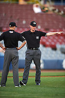 Umpire Ryan Wills signals safe after discussing the call with home plate umpire Jorge Teran (not shown) and third base umpire Ben Levin (left) during the second game of a doubleheader between the Trenton Thunder and Hartford Yard Goats on June 1, 2016 at Sen. Thomas J. Dodd Memorial Stadium in Norwich, Connecticut.  Trenton defeated Hartford 2-1.  (Mike Janes/Four Seam Images)