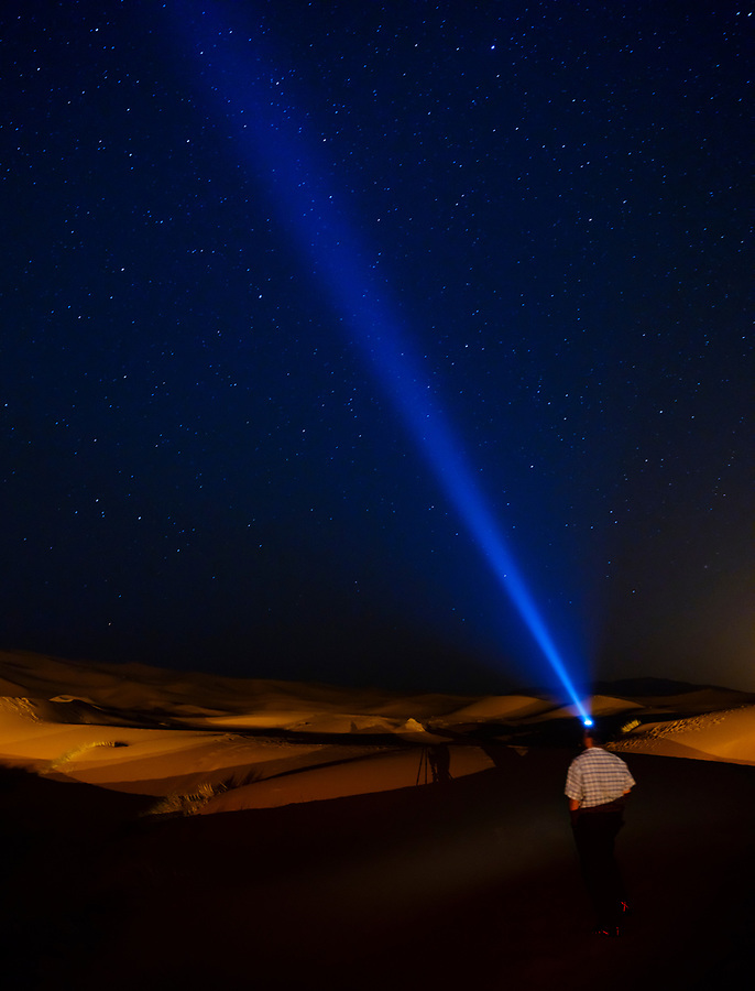 MEKNES - TAFILALET, MOROCCO - CIRCA APRIL 2017: Man looking the stars in the Moroccan Sahara desert using a headlamp.