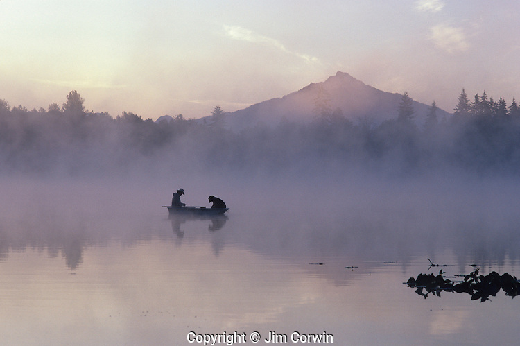 Sunrise at Lake Cassidy with Mount Pilchuck in fog with silhouetted fishermen in small rowboat getting ready to cast their lines, east of Marysville, Washington State USA